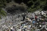 Television cameramen walk at a garbage dump where remains were found outside the mountain town of Cocula, near Iguala in the southwestern state of Guerrero